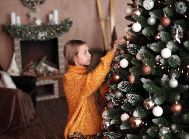 Schattig tienermeisje kerstboom versieren in haar woonkamer. het concept van kerstmis