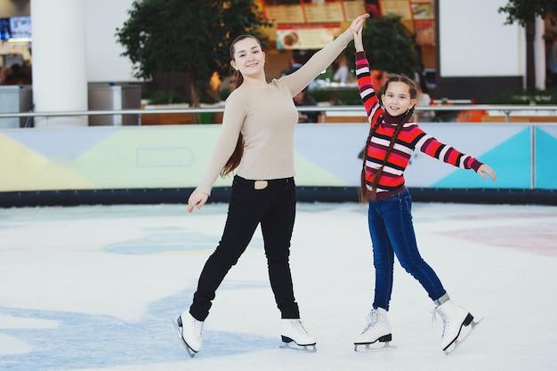 Schattig tienermeisje leert binnenshuis schaatsen op het ijs in het winkelcentrum