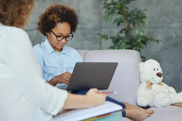 Schattig tienermeisje met een bril luistert naar haar vrouwelijke leraar die laptop gebruikt om te studeren terwijl ze een