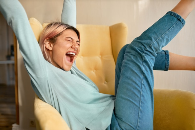 Schattig tienermeisje met neuspiercing en roze haren verhogen handen en voeten zittend comfortabel in fauteuil ogen sluiten en schreeuwen