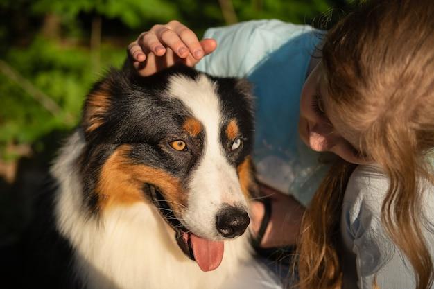 Schattig tienermeisje probeert australische herder te aaien. liefde en vriendschap
