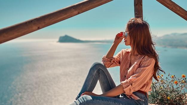 Schattig toeristenmeisje in zonnebril, gekleed in spijkerbroek en een shirt zit bij een houten hek bovenop een klif, bij een zee.