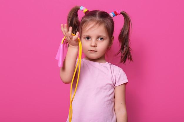 Schattig, verdrietig meisje houdt in de hand springtouw. klein kind wil met iemand spelen. schattige jongen met paardenstaarten en kleurrijke scrunchies, draagt t-shirt op roos.