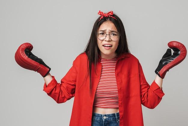 Schattig verward tienermeisje met een casual outfit die geïsoleerd over een grijze muur staat en bokshandschoenen draagt