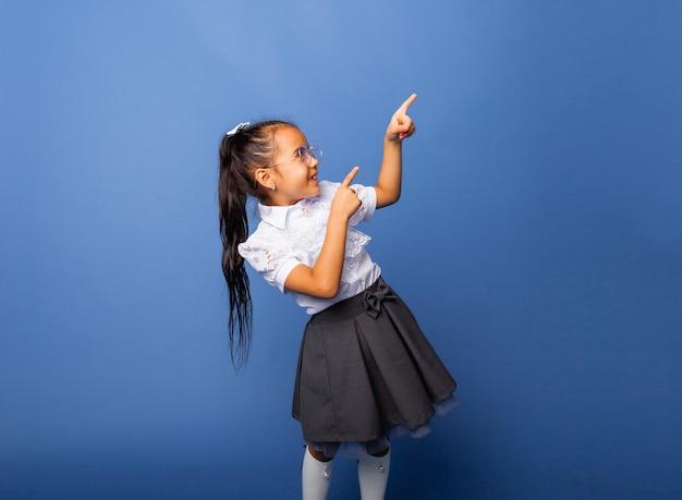 Schattig vrij vrolijk schoolmeisje wijzende vinger op zoek naar kant kopie ruimte geïsoleerd op blauwe achtergrond