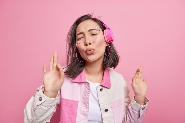 Schattig vrolijk aziatisch tienermeisje danst in moderne draadloze hoofdtelefoons houdt lippen gevouwen geniet van favoriete lied zingen melodie houdt handen omhoog geïsoleerd over roze muur. muziekliefhebber heeft plezier binnen
