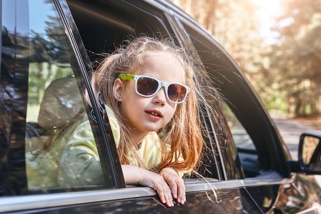Schattig vrolijk klein kaukasisch meisje dat in de auto zit en uit het raam kijkt familieweg