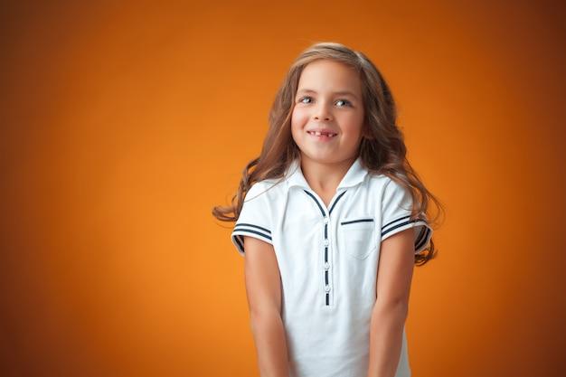 Schattig vrolijk klein meisje op oranje