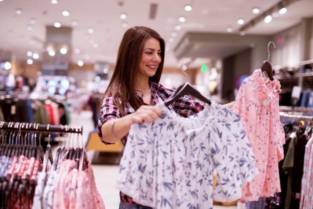 Schattig vrolijk meisje probeert te kiezen tussen twee rokken die ze vasthoudt terwijl ze in een winkel staat.