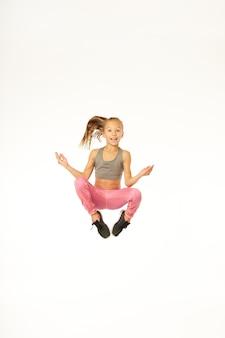 Schattig vrouwelijk kind dat naar de camera kijkt en glimlacht tijdens het springen en mediteren. geïsoleerd op witte achtergrond