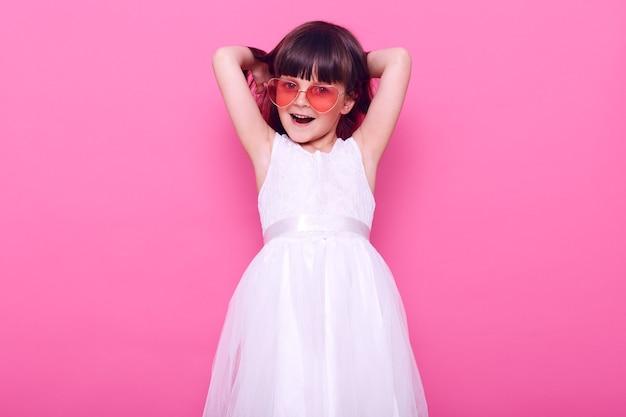 Schattig vrouwelijk kind met een gelukkige gezichtsuitdrukking die met opwinding naar voren kijkt, een stijlvolle witte jurk draagt, de handen omhoog houdt, geïsoleerd over de roze muur
