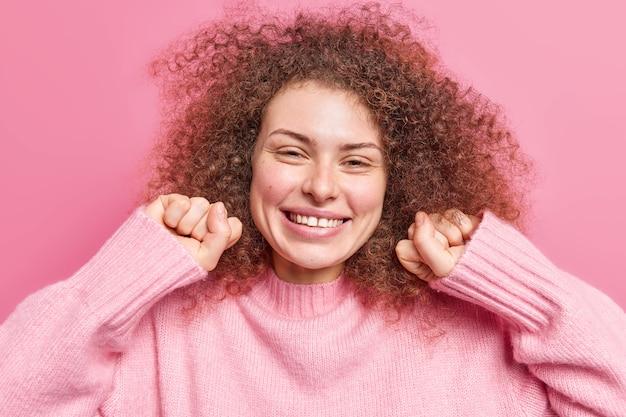 Schattig vrouwelijk meisje met krullend borstelig haar balt vuisten glimlacht graag ziet er gelukkig en ontspannen uit en draagt een casual trui geïsoleerd over roze muur. mensen oprechte emoties en gevoelens concept