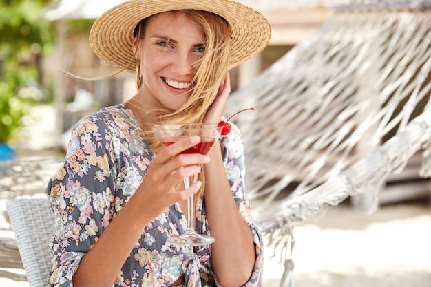 Schattig vrouwelijk model met een aantrekkelijke uitstraling draagt een strohoed en een shirt met bloemenprint, drinkt een verfrissende cocktail en is tevreden met een goed resort