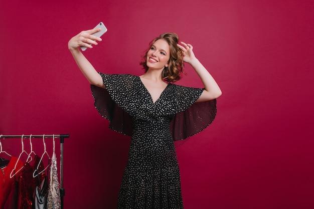 Schattig vrouwelijk model met mooie glimlach selfie maken in de kleedkamer