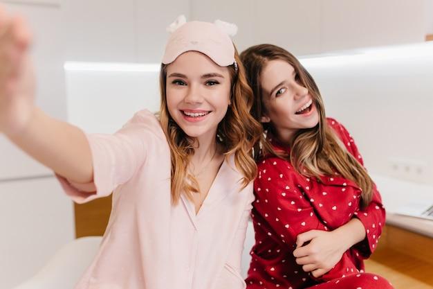 Schattig wit meisje met mooie glimlach selfie maken in lichte kamer. binnenopname van twee geweldige europese dames die van weekend genieten.