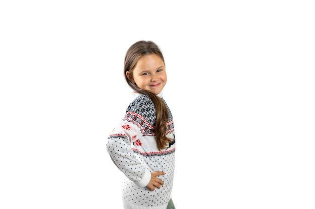 Schattig zesjarig meisje in witte gebreide kersttrui met rendieren poses met hand op taille isola...