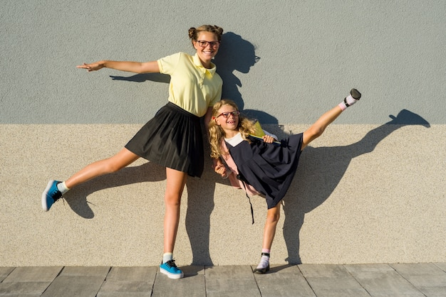 Schattig zusters schoolmeisje in schooluniform.