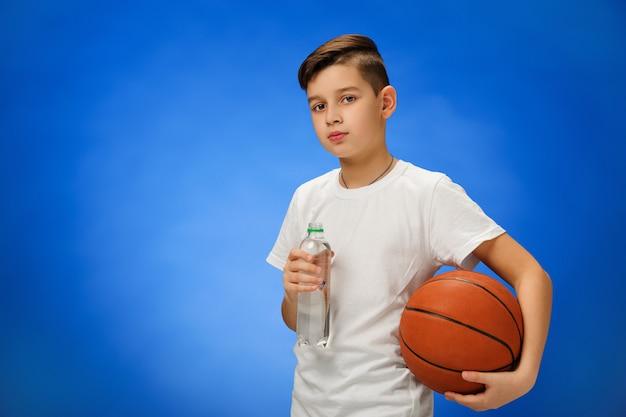 Schattige 11-jarige jongenskind met basketbal bal
