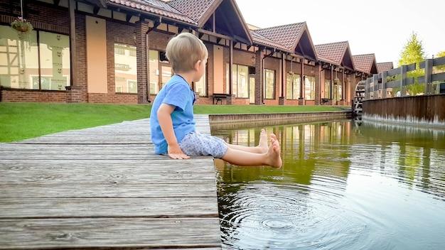 Schattige 3 jaar oude peuter jongen zittend op de rivieroever in kleine europese stad op zonnige zomerdag