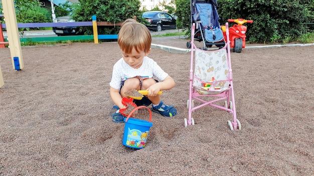 Schattige 3-jarige peuterjongen die in zandbak ligt met kleurrijk plastic speelgoed