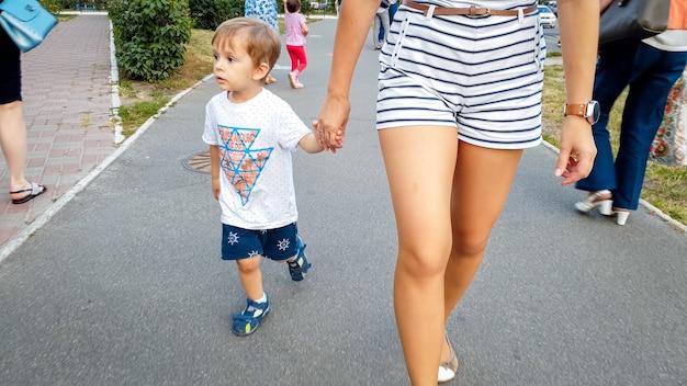 Schattige 3-jarige peuterjongen die zijn moeder met de hand vasthoudt en op straat loopt