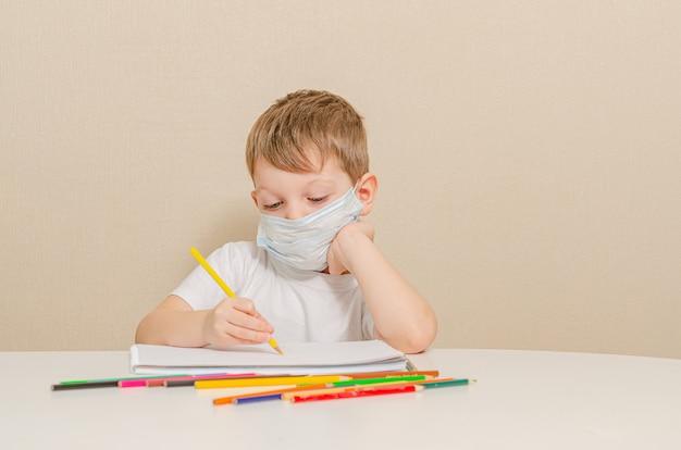 Schattige 4 jaar oude jongen in medische masker zit thuis in quarantaine. entertainment voor het kind tijdens quarantaine - tekenen.