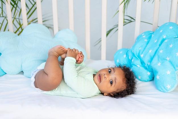 Schattige afrikaanse baby ligt thuis op het bed op het katoenen bed met zijn benen omhoog en speelt met zijn handen.