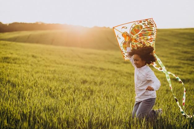 Schattige afrikaanse babymeisje op het veld op de zonsondergang spelen met kite
