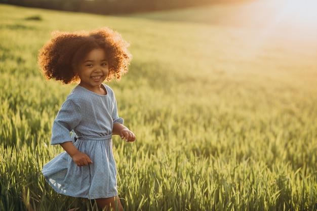 Schattige afrikaanse babymeisje op het veld op de zonsondergang