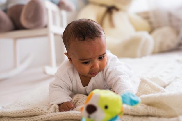 Schattige afro-amerikaanse babyjongen spelen met speelgoed binnenshuis