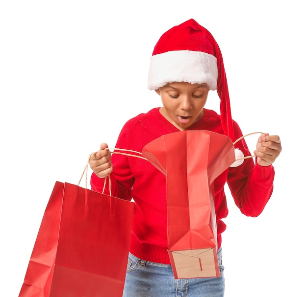 Schattige afro-amerikaanse jongen in kerstmuts en met boodschappentassen