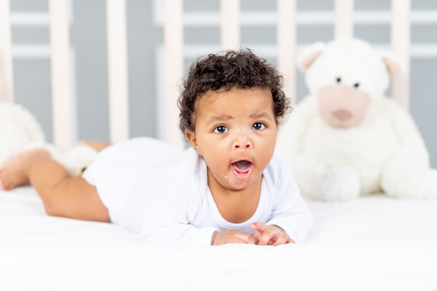 Schattige afro-amerikaanse kleine baby die in bed ligt om te slapen en te geeuwen