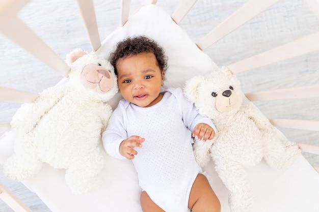 Schattige afro-amerikaanse kleine baby in wit slaapbed met beerspeelgoed