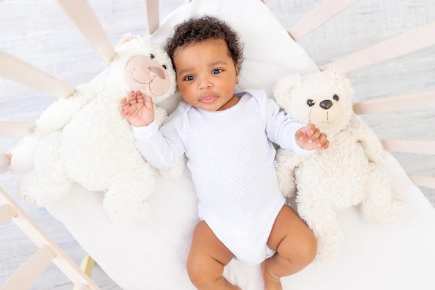 Schattige afro-amerikaanse kleine baby in wit slaapbed met berenspeelgoed