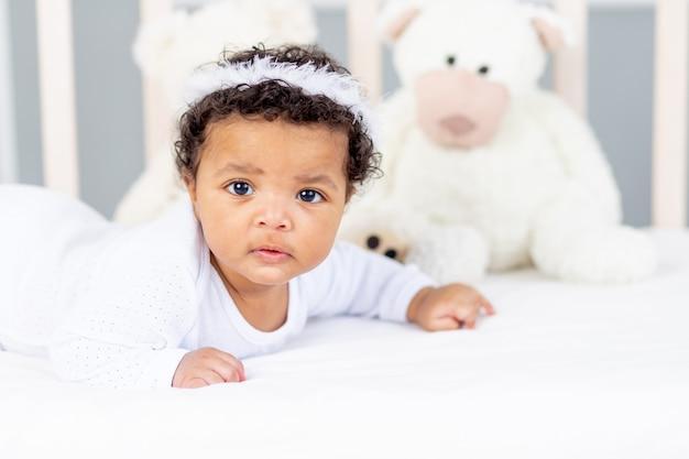 Schattige afro-amerikaanse kleine baby liggend in bed om te slapen met engelenhoofdband