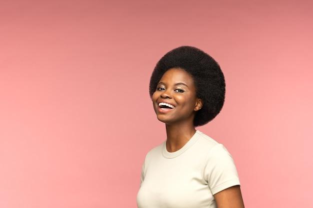 Schattige afro-amerikaanse vrouw met mooie afro kapsel lachen geïsoleerde roze studio achtergrond