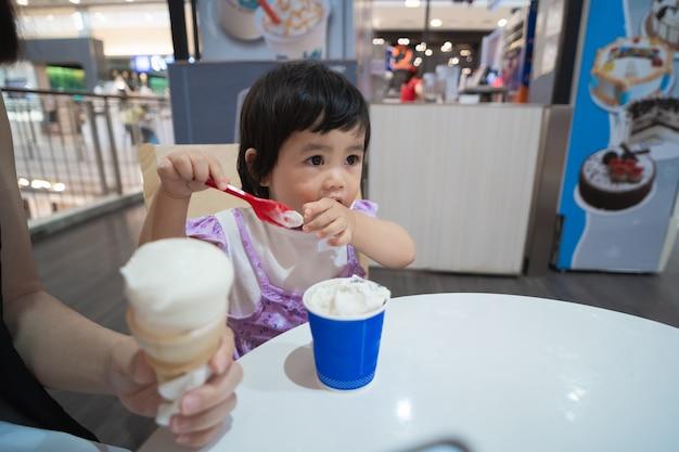 Schattige aziatische baby eten van ijs in het restaurant