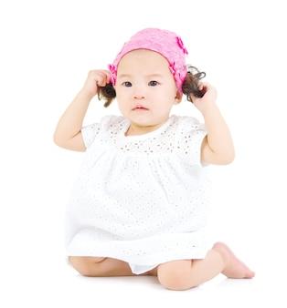Schattige aziatische baby zittend op de vloer.