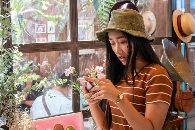 Schattige aziatische jonge zakenvrouw in het café met behulp van de mobiele telefoon