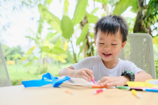 Schattige aziatische kleuterjongen die diy draagtas kleurt met makers thuis, kind geniet van knutselproject