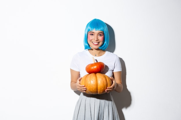 Schattige aziatische vrouw in blauwe pruik met twee schattige pompoenen en glimlachend in de camera, schoolmeisje outfit dragen voor halloween-feest.