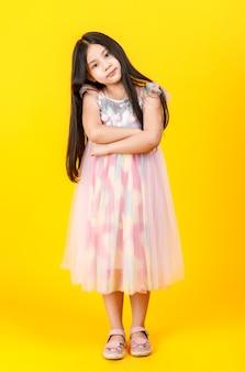 Schattige aziatische vrouwelijke jongen poseren voor de camera met zelfvertrouwen op gele achtergrond.