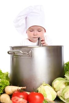 Schattige baby chef-kok met grote pot en groenten