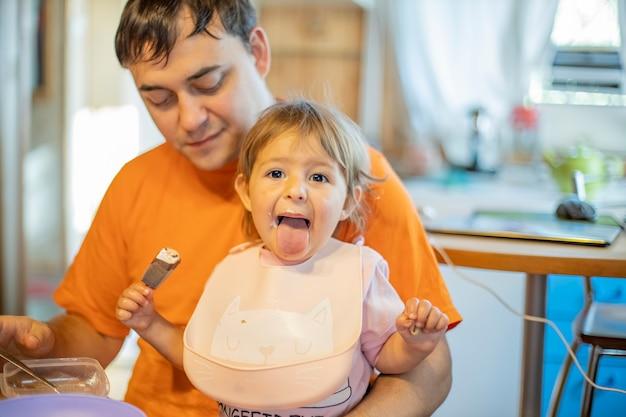 Schattige baby die roomijs eet en tong toont. vader die babylanch voedt. grappig kind aan het eten