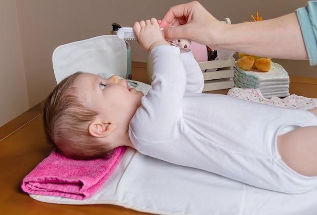 Schattige baby die speelt en kam grijpt in de hand van haar moeder