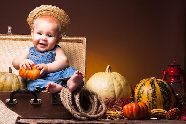 Schattige baby die zich voordeed op de achtergrond van pompoenen. dankzeggingsgroeten