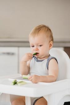 Schattige baby eet alleen in zijn kinderstoel