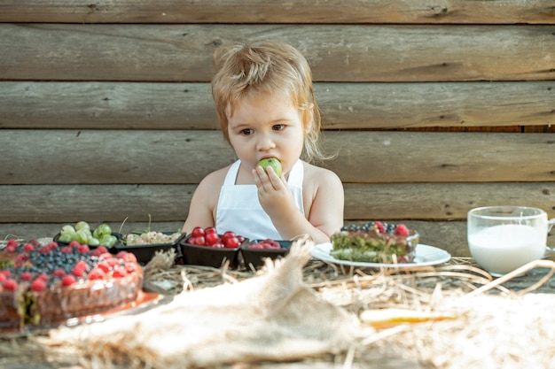 Schattige baby eet groene appel aan tafel met bessen framboos kruisbes kersen bessen fruit cake en kopje melk buiten op houten