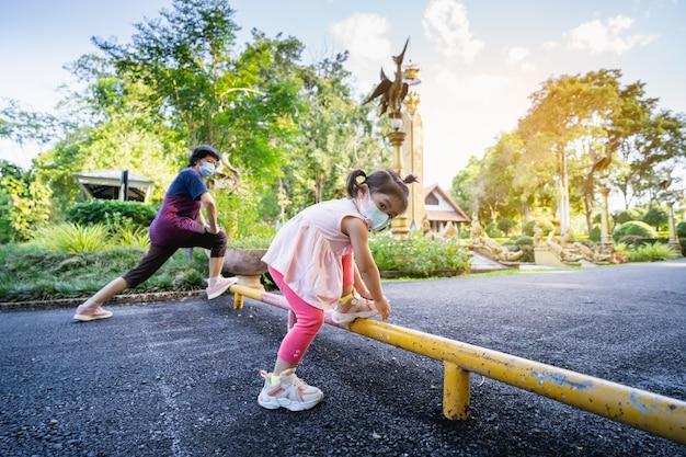 Schattige baby en haar oma dragen chirurgisch masker en strekken zich uit voordat ze in het park rennen