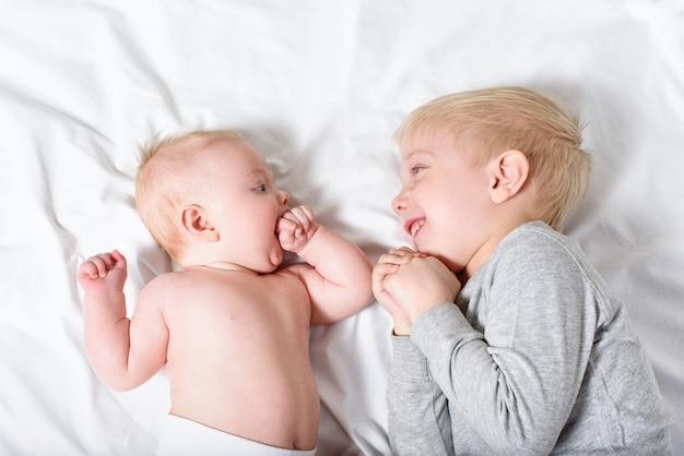 Schattige baby en lachende oudere broer liggen op het bed